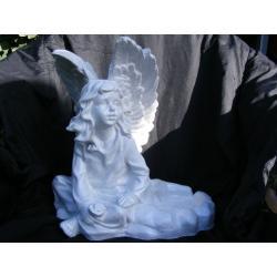 Duży,siedzący anioł z różyczką